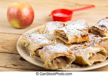 Apple pie sliced on the plate with powdered sugar