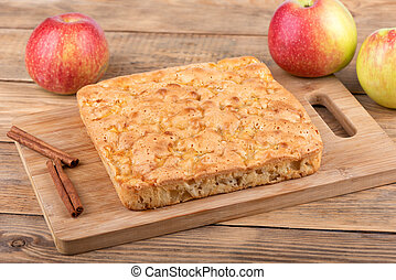 Apple pie sprinkled with cinnamon on a cutting board.