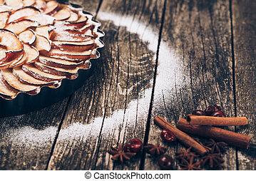 Apple pie tart on rustic wooden background. Ingredients - apples and cinnamon .
