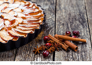 Apple pie tart on rustic wooden background. Top view.