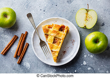Apple pie with caramel on a white plate. Grey background. Top view.