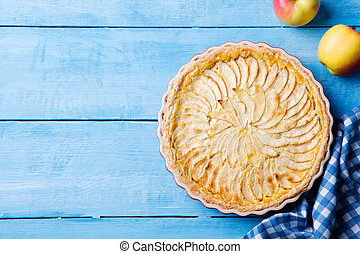 Apple pie with cream on a blue wooden background. Top view. Copy space