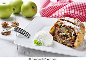 apple strudel on a dish with fresh apples and nuts