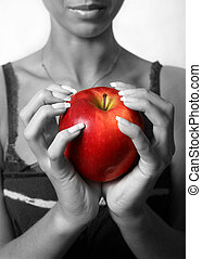 Apple - The girl holds in hands red an apple. Partial...