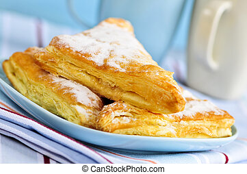 Apple turnovers pastries with coffee cups in the background