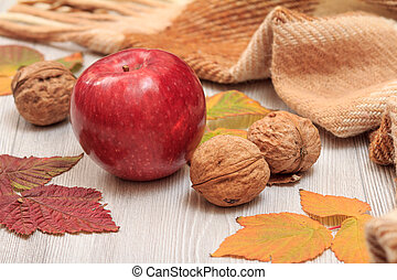 Apple, walnuts, checkered plaid and dry leaves on wooden boards. Still llife in autumn theme.