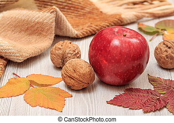 Apple, walnuts, checkered plaid and dry leaves on wooden boards. An autumn theme.