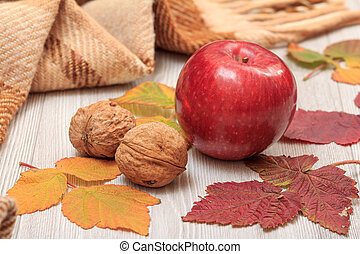 Apple, walnuts, checkered plaid and dry leaves on wooden boards. An autumn composition.