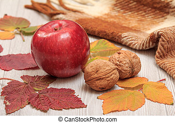 Apple, walnuts, checkered plaid and dry leaves on wooden boards. An autumn still llife.
