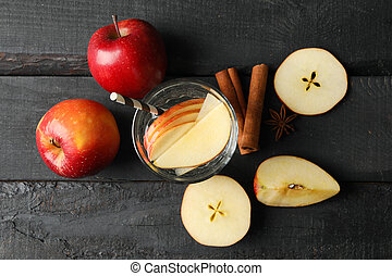 Apple, water and cinnamon on wooden background, top view