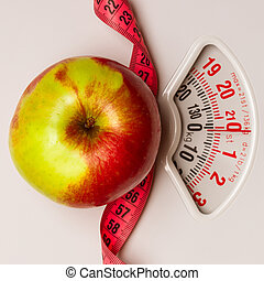 Apple with measuring tape on weight scale. Dieting