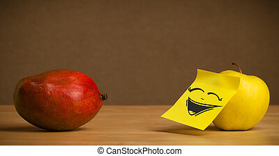 Apple with post-it note laughing on mango - Apple with...