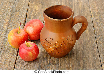 Apples and crock with cider on a wooden table.
