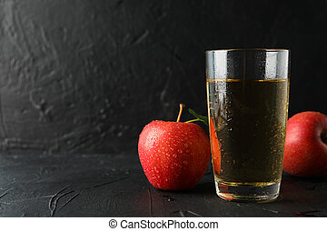 Apples and glass with juice on black background, copy space
