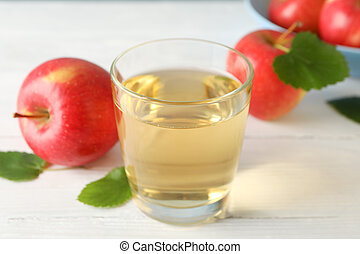 Apples and glass with juice on wooden background, space for text