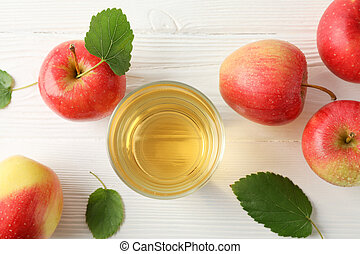 Apples and glass with juice on wooden background, top view