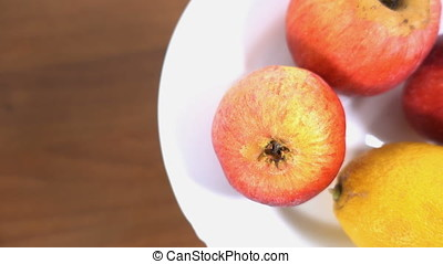 Apples and lemon rotating on a plate against wooden table