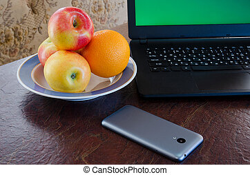 Apples and oranges on a plate next to a laptop, smart phone on the table. Healthy break