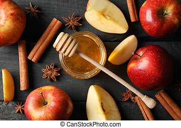 Apples, cinnamon and honey on wooden background, top view