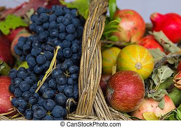 Apples, grapes, pumpkins in a wicker basket