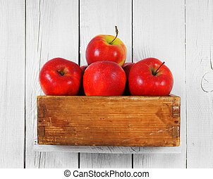 Apples in a box on wooden shelf.