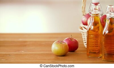 apples in basket and bottles of juice on table - fruits,...