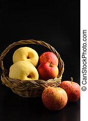 Apples in basket on a black background