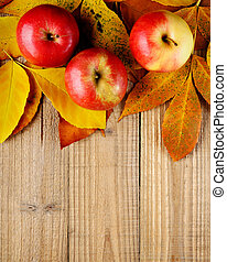 Apples on autumn leaves on wooden background