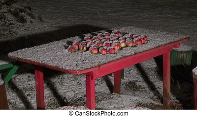 Apples on table and falling snow