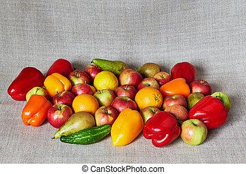 Apples, paprika, pear, lemon and orange on a gray canvas