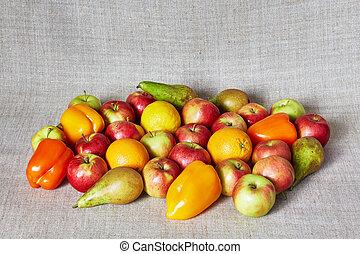 Apples, paprika, pear, orange and lemon on a gray canvas