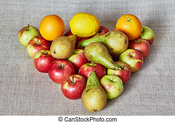 Apples, pear, orange and lemon on a gray canvas
