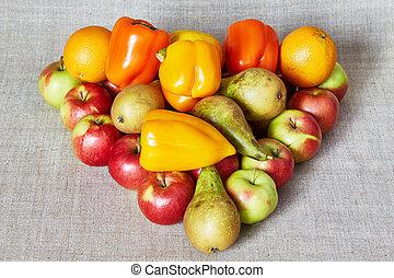 Apples, pear, paprika, orange and lemon on a gray canvas