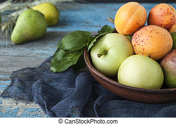 Apples, pears and apricots in a plate on a wooden table