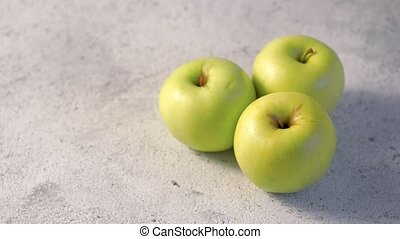 Apples rotating, copy space for text - Three organic green...
