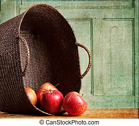 Apples spilling out of basket on grunge background
