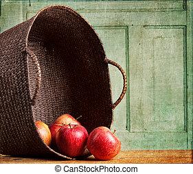 Apples spilling out of basket on grunge background - Apples...