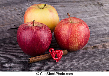 Apples with cinnamon on wooden background
