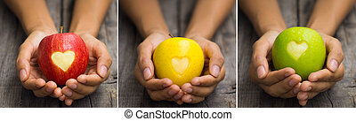 Apples with engraved hearts - A person holding three...
