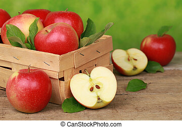 Apples with leaves in a wooden box on a table with green...