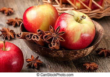 Apples with spices on a wooden background