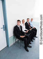 Applicants Sitting On Chair In Office - Group Of Applicants...