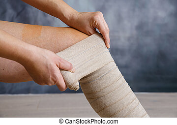 Application of elastic compression bandage - Woman patient...