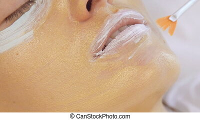 Application of golden masks on the face of the model. Close up