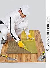 applies reinforce fiber mesh on tile adhesive on wooden floor