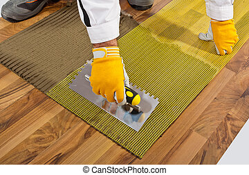 applies tile adhesive on wooden floor with reinforce fiber mesh