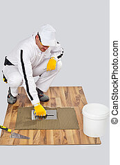 Appling Tile Adhesive with Notched Trowel on a old wood Floor