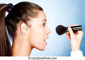 teen girl apply powder with cosmetic brush, profile, studio shot