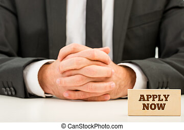 Apply Now Text on Small Wooden Piece in Front Businessman