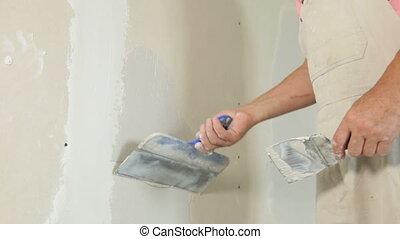 Applying a Coat of Plaster - Man's hand applying plaster on...